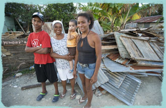 Marisel and family stand in front of demolished old house